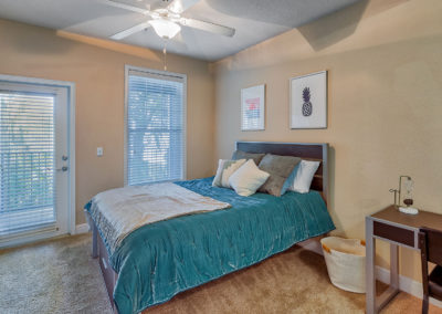 Bedroom With a Made Bed at Lyons Corner Apartments